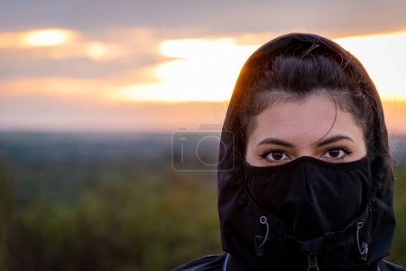 Photo for Very powerful look of a woman that transmits strength, security, serenity. Covered with a black hood and a black mask in a sunset with the background out of focus - Royalty Free Image
