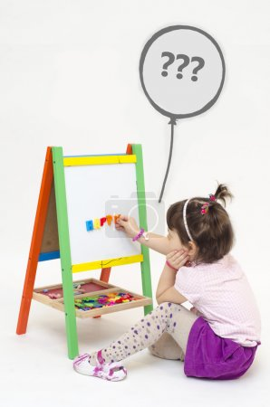 Musingly girl glues magnetic letters on white board wondering