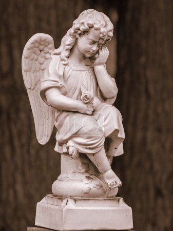 Angel statue in front of a tree
