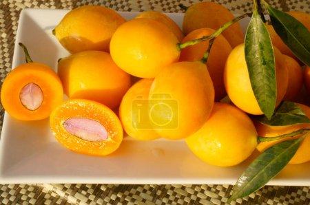 """Ciruela mariana, Gandaria, Mayongchid, Maprang, Ciruela Mango.Lat: """"Bouea Macrophylla"""" .Mariana frutos de ciruela en un plato rectangular blanco. Hay una ciruela cortada.."""