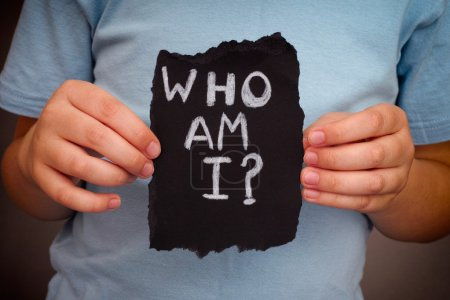 Photo for Child holds piece of black paper with question Who am I?. Close up. - Royalty Free Image
