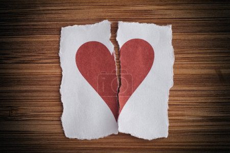 Photo for Broken paper heart on a wooden background. Light noise effect added. Vignette. - Royalty Free Image