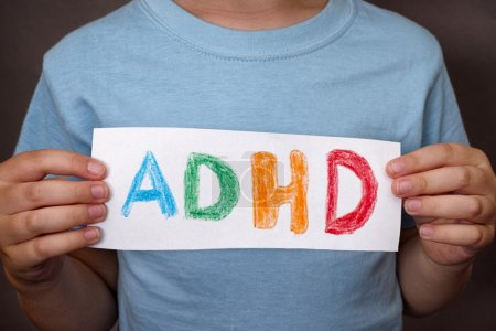 Young boy holds ADHD text written on sheet of paper