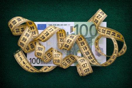 Photo pour Ruban à mesurer de plus de cent euros sur fond vert. Gros plan . - image libre de droit