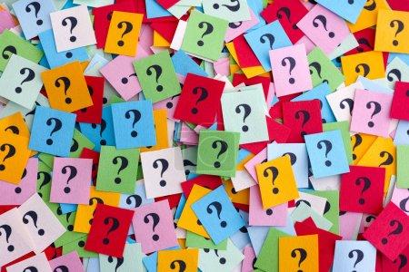 Foto de Demasiadas preguntas. Pila de billetes de papel de colores con signos de interrogación. Closeup. - Imagen libre de derechos