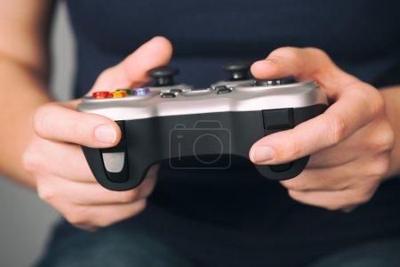 Foto de Mujer joven juega videojuegos usando un gamepad. Cierre para arriba. - Imagen libre de derechos