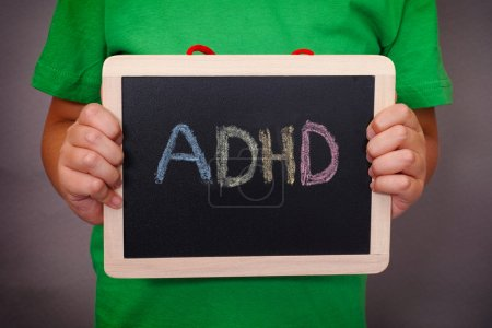 Young boy holds ADHD text written on blackboard