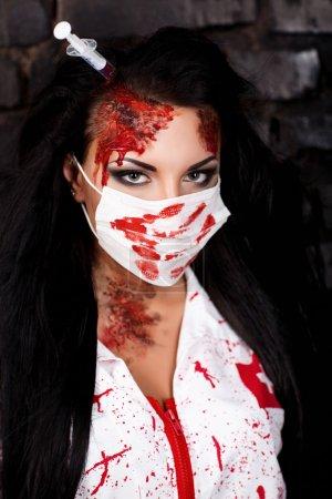 Photo pour Belle infirmière tueuse aux cheveux noirs de l'hôpital. La seringue sanglante colle dans la tête et le cerveau suit. jeu de rôle maison folle, robe sexy manteau blanc meurtrissures sang sale. Joyeux halloween - image libre de droit