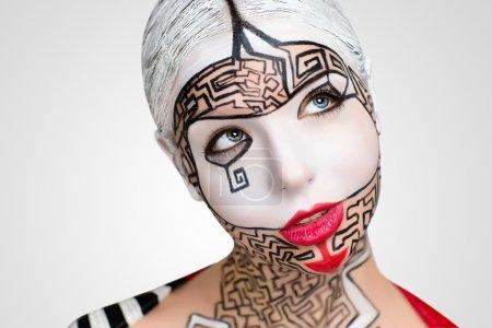 Photo pour Belle femme avec du maquillage de l'art conceptuel, vue d'ensemble blanc sur le visage, les lèvres rouges, les lignes noires du puzzle labyrinthe, bouchent nouveau portrait. Photo avec grand espace libre, espace, lieu d'inscription de texte, boutons - image libre de droit