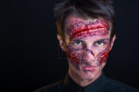 Foto de Hombre con cara sangrante. Maquillaje profesional para película de terror (maquillaje faceart bodyart), cosméticos. Foto realista. Se puede utilizar para la fiesta de Halloween, vampiro, salón, estudio de terror, loco, guerrero - Imagen libre de derechos