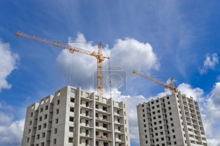Multi-storey houses under construction and high-rise crane