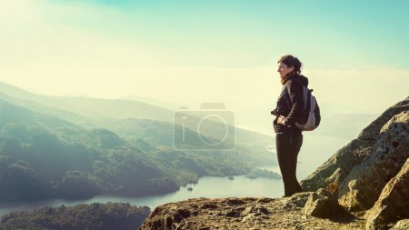 Female hiker on top of the mountain enjoying valley view, Ben A'an, Loch Katrina, Highlands, Scotland, UK, insurance concept