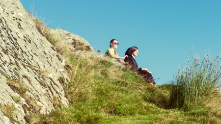 Two female hikers on top of the mountain taking a break and enjoying a valley view, Ben A'an, Loch Katrina, Highlands, Scotland, UK