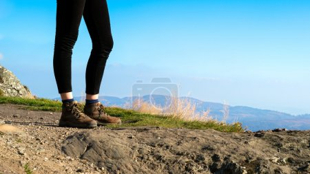 Unrecognisable female hiker on top of the mountain wearing hiking boots, Ben A'an, Loch Katrine, Highlands, Scotland, UK