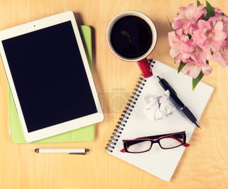 Photo for Office table with digital tablet, reading glasses cup of coffee and notepad. View from above with copy space - Royalty Free Image