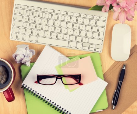 Photo for Messy office table with notepad, computer, reading glasses and coffee cup. View from above with copy space - Royalty Free Image