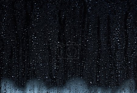 Rain droplets running down a window, abstract backlight background
