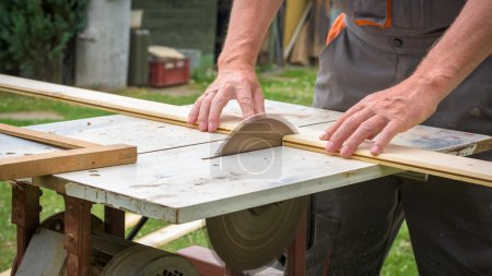 Carpenter working with electric buzz saw cutting wooden boards
