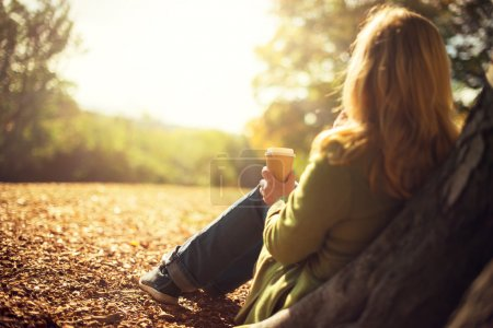 Photo pour Concept de l'automne, anonyme femme appréciant la tasse de café à emporter sur cols ensoleillés tomber jour - image libre de droit
