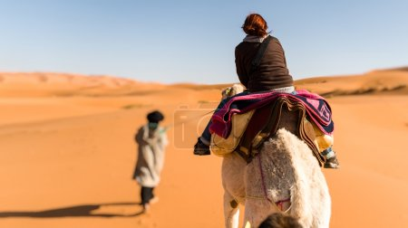 Woman traveling on camel led by a berber nomad, back view