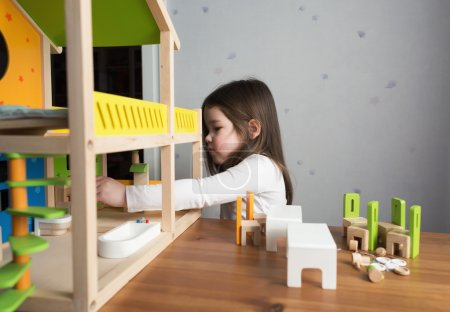 A little girl playing with dollhouse
