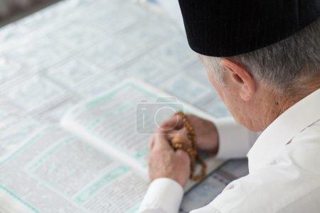 An old man reading Koran. Selective focus