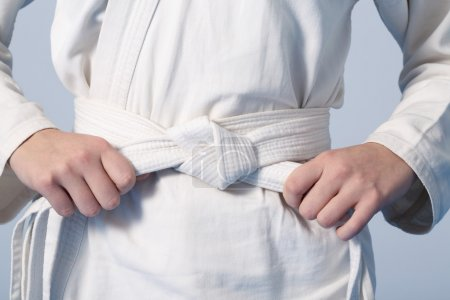 Hands tightening white belt on a teenage dressed in kimono