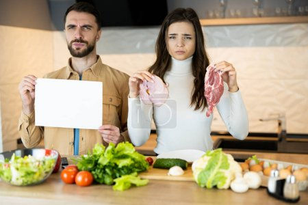 Photo for Young vegetarian couple is showing that they dont like eating meat and prefer fresh vegetables to it. Healthy lifestyle without meat . - Royalty Free Image