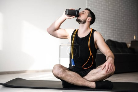 Photo for Man drinks water after hard workout and sits with crossing legs. Black yoga mat. Man is very tired after yoga practice. Take care of youself concept. Drink more water. Smart modern room on background - Royalty Free Image