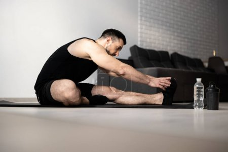 Photo for Stretch body exercise. Yoga position. Man stretching before workout. Black sportswear. Athletic man warming up on black yoga mat. Sports during quarantine. Remember to warm up before hard workout - Royalty Free Image