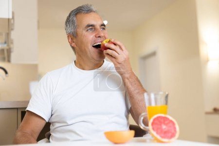 Photo for Happy adult man eating fruits and healthy food on breakfast. Morning routine concept. Cut halves of grapefruit and glass of orange juice on table. Cozy modern kitchen on background - Royalty Free Image
