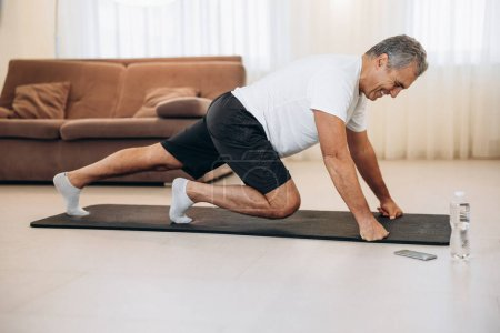 Photo for Elderly man doing mountain climber exercises on black yoga mat. Morning workout. Modern living room on background. Plastic bottle of water. Hard workout. Training at home. Elderly sport concept - Royalty Free Image