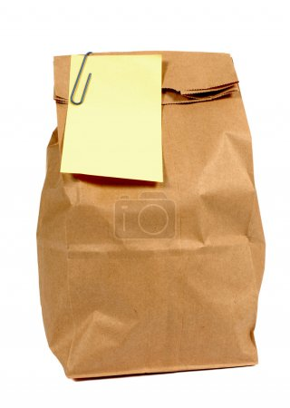 Brown paper lunch or groceries bag with yellow post it style sticky note
