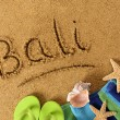 The word Bali written on a sandy beach, with beach towel, starfish and flip flops.