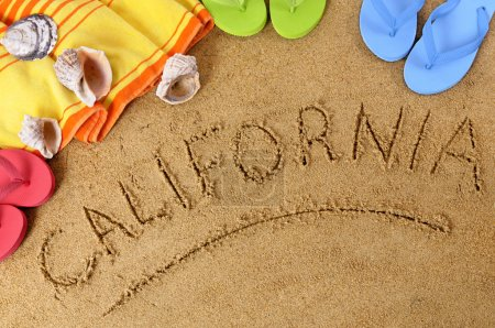 Photo for Beach background with towel and flip flops and the word California written in sand. - Royalty Free Image