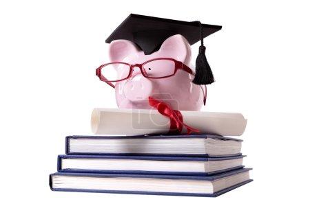 Photo pour Tirelire rose habillée en diplômée d'université avec panneau de mortier, verres et diplôme debout sur une petite pile de livres. Isolé sur blanc . - image libre de droit