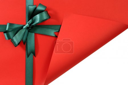 Green gift ribbon bow on plain red background pape...