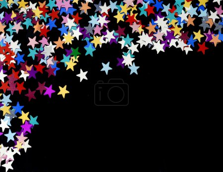 Photo for Starry night background; coloured stars scattered on a plain black background, copy space - Royalty Free Image