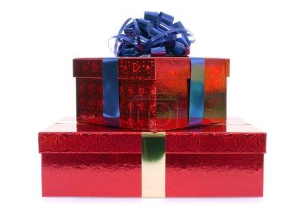 Photo pour Petite pile de boîtes-cadeaux rouges avec ruban bleu arc isolé sur fond blanc - image libre de droit