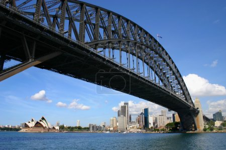 Photo for Sydney harbour bridge looking up from under with financial district and opera house in distance - Royalty Free Image