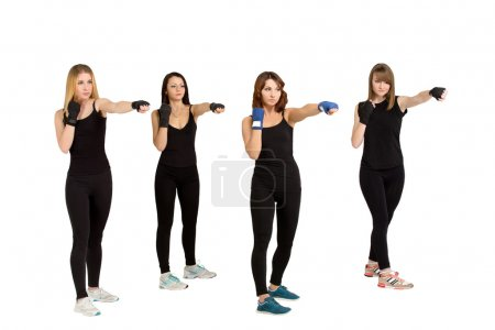 Photo for Fitness training studio shot - four young slim women in black sportswear making tae bo exercises isolated at white background. Fitness woman group. - Royalty Free Image