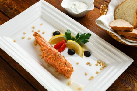 Photo for Restaurant food, salmon dish. Hot fish dish. Barbecue grilled fish dish. Restaurant food catering. Salmon barbecue grill roasted with lemon and olives. Grilled salmon served in restaurant closeup. - Royalty Free Image