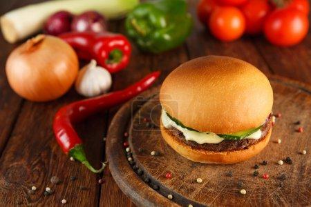 Photo for Classic american burger food. Hamburger at wood. Wooden desk with hamburger and fresh vegetables composition. Burger with cheese, beef, cucumber, lettuce. Cheeseburger at wooden background. - Royalty Free Image