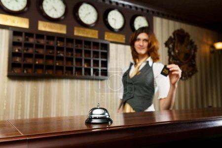 Foto de Hotel moderno Mostrador recepción con campana. Recepcionista del hotel le da una tarjeta a un invitado. Recepcionista mujer mostrador desenfocado. Enfoque selectivo en campana de contador. Viaje, concepto de hospitalidad. - Imagen libre de derechos