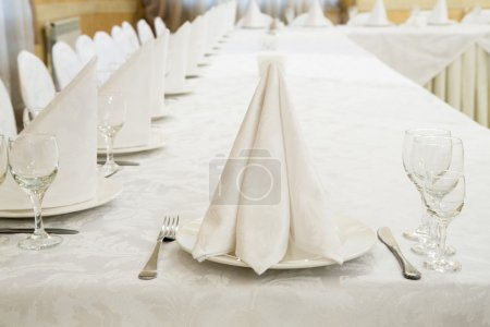 Photo for Beautifully organized event, glasses, napkin at served festive white table ready.  Event in restaurant. Banquet, wedding decor, celebration. Catering and event. Wedding tables. Large restaurant hall. - Royalty Free Image
