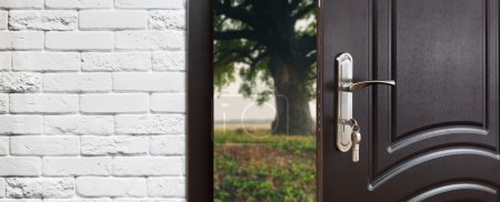 Entrance door half opened to the nature background