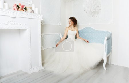 Photo for Wedding dress fashion. Beautiful young bride in vintage wedding dress indoors. White wedding dress at model. Girl shows wedding fashion in decorated shabby chic interior with flowers, high key. - Royalty Free Image