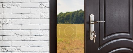 Photo for Entrance door half opened to nature background. Door handle, door lock. Exit outdoors. Opening door. Entrance to the house. Door at white brick wall, summer field and forest, freedom concept. - Royalty Free Image
