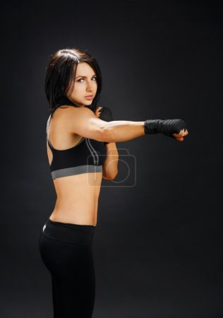 Strong body - fitness fighter girl shows muscle.