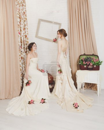 Foto de Wedding dress fashion. Two beautiful young brides in vintage wedding dresses indoors. Rustic wedding dresses at models. Girls in champaigne color dresses in decorated interior with flowers, high key. - Imagen libre de derechos